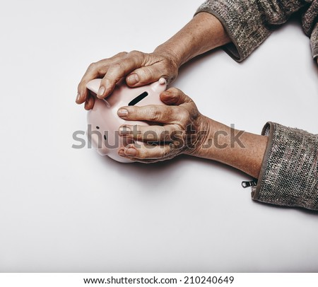 Top view of senior woman hands holding a piggy bank on grey surface. Elderly hands grabbing a small piggybank. Concept of secure investments. - stock photo