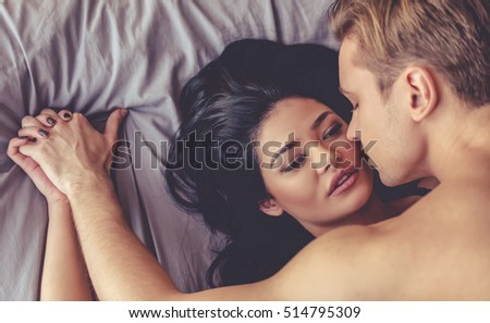 Top view of sensual beautiful young couple having sex on bed