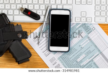 Top view of service weapon, keyboard, pen, thumb drive and IRS tax form on desktop. Audit concept.  - stock photo
