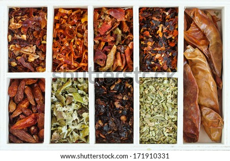 top view of set of hot spice chili peppers in wooden box - stock photo