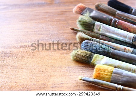 top view of set of used paint brushes over wooden table - stock photo