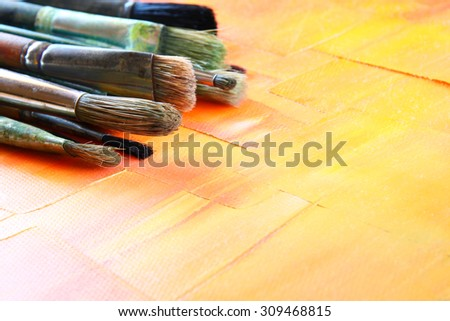 top view of set of used paint brushes over wooden table. close up image selective focus