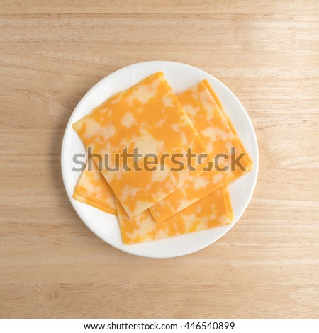 Top view of several slices of Colby-Jack cheese on a white plate atop a wood table illuminated with natural light.