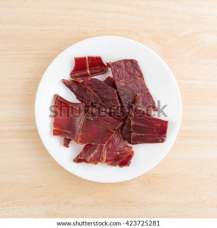 Top view of several slices of hardwood smoked beef jerky on a white plate atop a wood table top. - stock photo
