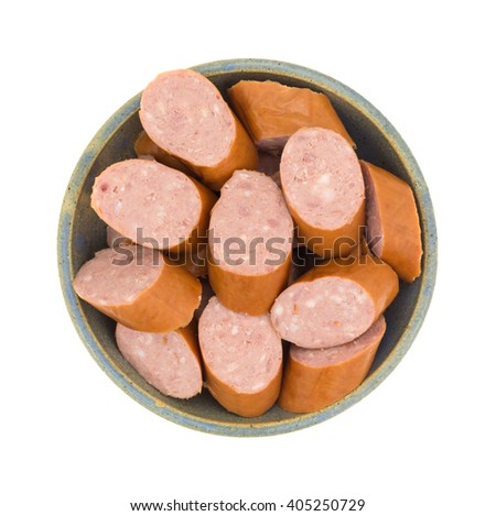 Top view of several slices of reduced calorie kielbasa sausage in an old stoneware bowl isolated on a white background. - stock photo