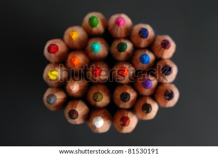 Top view of sheaf of colored pencils, isolated on a black background - stock photo