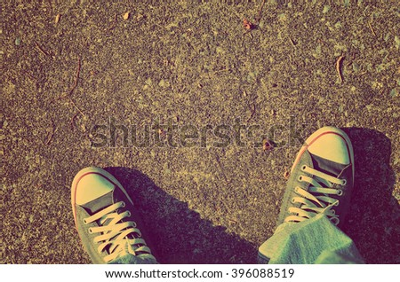 Top view of shoes and blue jean on street, selfie, travel concept.Retro color style.