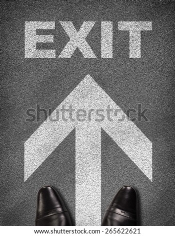 Top view of shoes standing on asphalt road with arrow and word exit. Business concept - stock photo