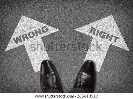 Top view of shoes standing on asphalt road with two arrows. Labels wrong and right. Business concept - stock photo
