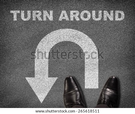 Top view of shoes standing on asphalt road with U-turn sign and text turn around. Business concept - stock photo