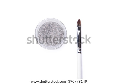 Top view of silver glitter and make-up brush, isolated on white background