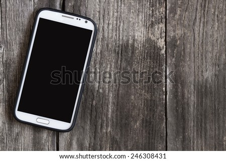 top view of single smart phone with black, blank screen for your design on vintage grunge wooden table - stock photo