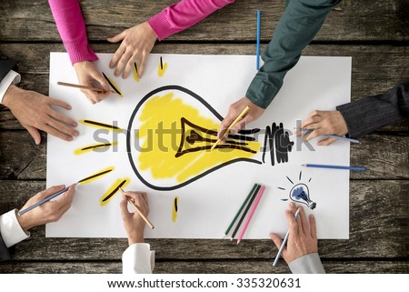 Top view of six people, men and women, drawing bright yellow light bulb on a large sheet of paper or placard. Conceptual of teamwork, research, education and innovation. - stock photo