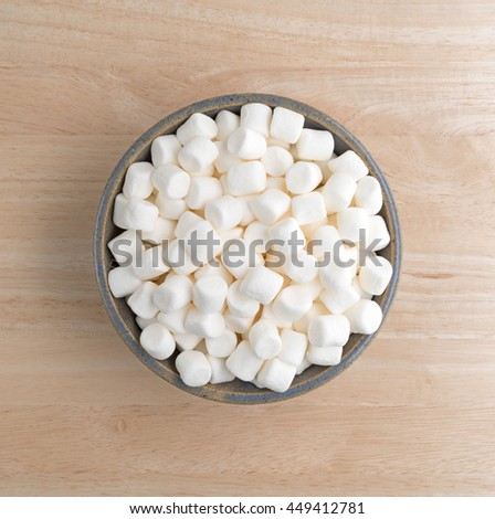 Top view of small bite size marshmallows filling an old stoneware bowl on a wood table. - stock photo