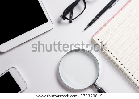 top view of smartphone ,tablet, glasses, pencil, notebook and magnifier on white background , concept  for find business problem