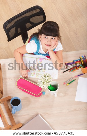 Top view of smiling little girl drawing picture with multicoloured pencils while sitting at table at home and looking away. - stock photo