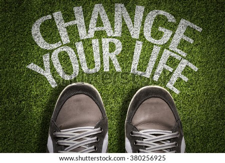Top View of Sneakers on the grass with the text: Change Your Life - stock photo