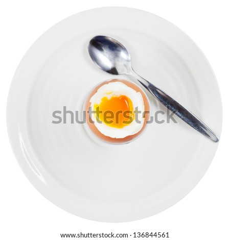 top view of soft boiled egg in egg cup and spoon on white plate isolated on white - stock photo