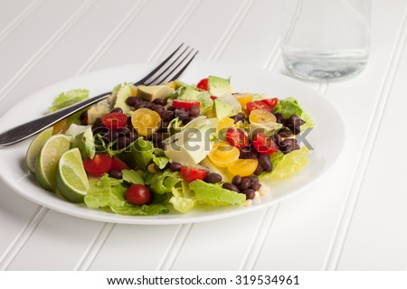 Top view of southwest black bean, lime, cilantro, tomato, and avocado salad on a vintage antique plate with water - stock photo