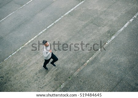 Top view of sporty man running in winter on urban asphalt. Male runner training outside.