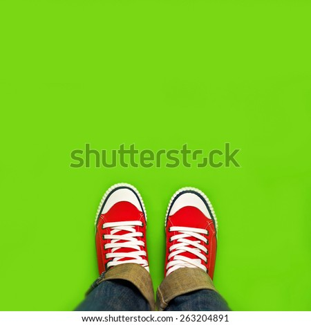 Top View of Springtime Youth Lifestyle Concept for New Beginnings, Woman with Red Sneakers Standing on Green Spring Background as Blank Copy Space. - stock photo