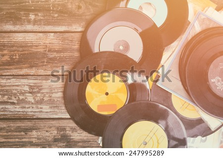 top view of stack of records over wooden table. retro style filter - stock photo