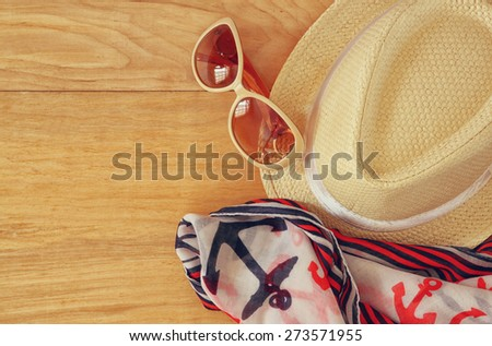 top view of stylish hat woman sunglasses and tablet fashion nautical scarf over wooden table. vacation and travel concept  - stock photo