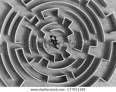Top view of successful businessman standing in center of labyrinth - stock photo