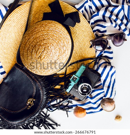 Top view of summer accessories for modern woman on her vacation. Straw hat,  camera, stylish sunglasses, black leather boho bag and striped beach dress on white floor.  - stock photo