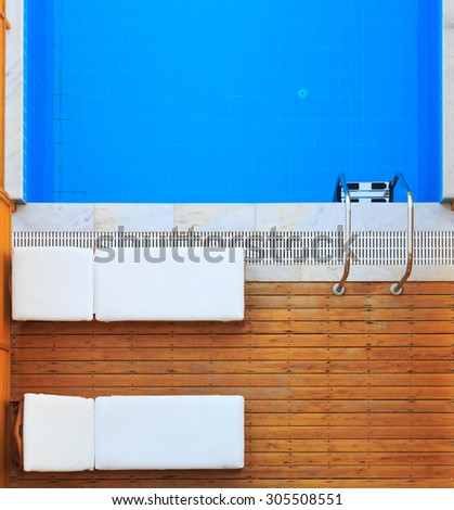 Top view of sunbeds on wooden floor near private pool