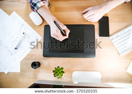 Top view of table of graphic designer using black pen tablet with stylus - stock photo