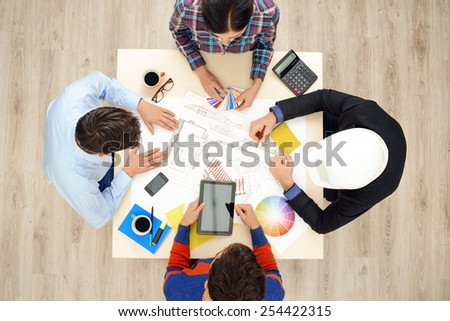 Top view of table with group of creative people working on business project. Team discussing construction issues - stock photo