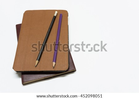 top view of tablet with brown leather diary and pencil on white background - stock photo
