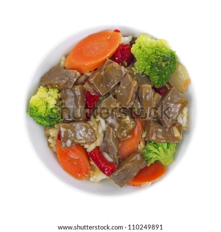 Top view of takeout beef teriyaki with colorful vegetables on a white background.