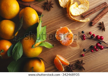 Top view of tangerines with leaves in Christmas decor with Christmas tree, dry orange and berries over old wooden table. Dark rustic style - stock photo