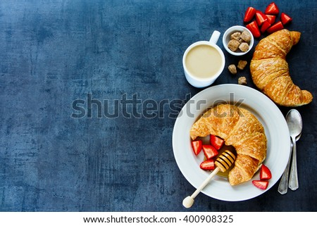 Top view of tasty breakfast table with fresh croissants, honey, ripe strawberry and coffee, border. Health and diet concept. Vintage background with space for text. - stock photo
