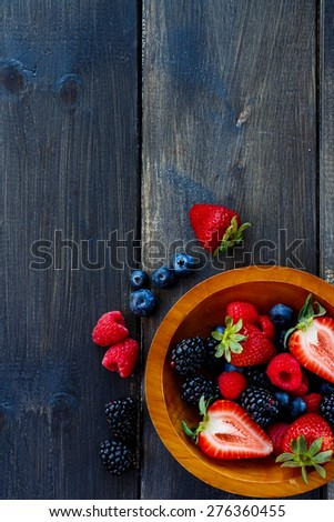 Top view of tasty summer berries (strawberries, raspberries, blueberries and blackberries) in wooden bowls on dark table. Agriculture, Gardening, Harvest Concept. Background with space for text. - stock photo