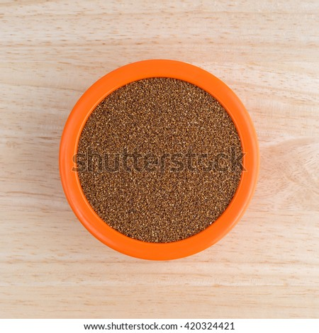 Top view of teff grain filling an orange bowl atop a wood table top. - stock photo