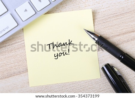 Top view of Thank You sticky note pasted on the wooden desk with keyboard and pen aside. - stock photo