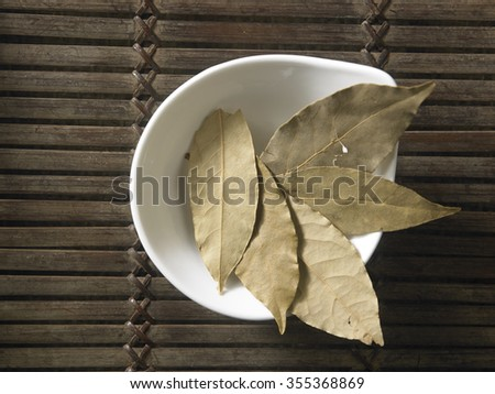 top view of the bay leaves on the wooden background - stock photo