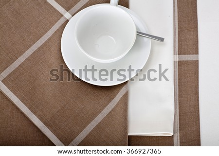 Top view of the beautifully decorated table with white plate, teacup and linen napkins on luxurious tablecloth