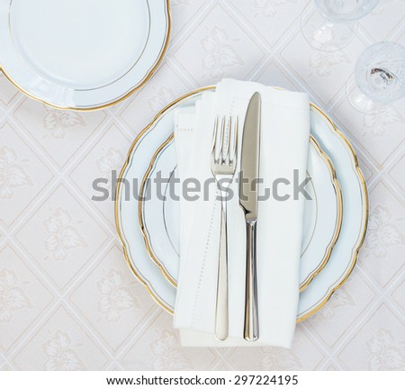 Top view of the beautifully decorated table with white plates, crystal glasses, linen napkin  and cutlery on luxurious tablecloths - stock photo