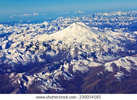 Top view of the Caucasus mountains with snow covered top of Elbrus  - stock photo
