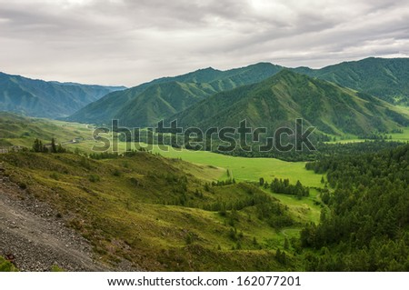 Top view of the mountains, the valley, the road and the forest on a cloudy day. - stock photo