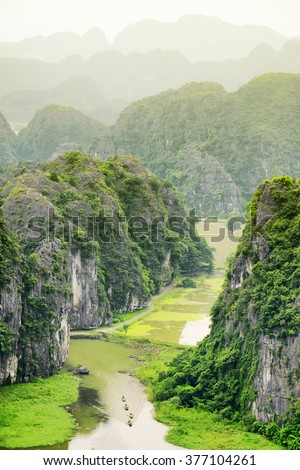 Top view of the Ngo Dong River and boats at the Tam Coc portion, Ninh Binh Province, Vietnam. Karst towers are visible in background. The Tam Coc is a popular tourist attraction in Vietnam.