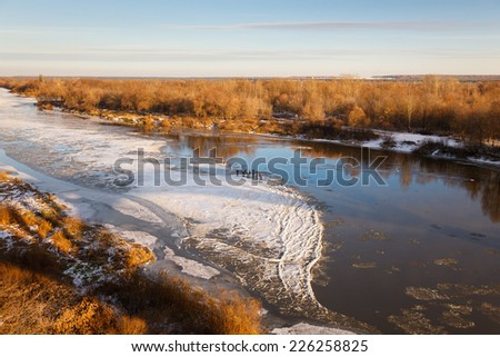 top view of the river covered with thin ice with wormwood