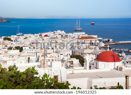 Top view of the town and port of Mykonos Island and a sailing boat in the blue sea ... - stock photo