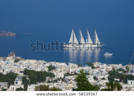 Top view of the town of Mykonos Island and a sailing ship in the blue sea ... - stock photo