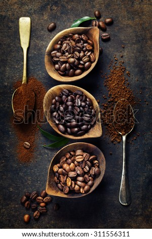 Top view of three different varieties of coffee beans on dark vintage background - stock photo