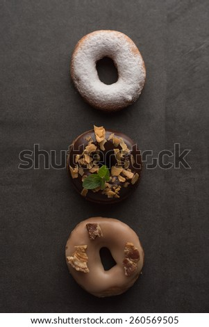 Top view of three donuts on dark stone background - stock photo